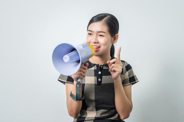 Belle jeune femme asiatique tenant haut-parleur, cheveux noirs.