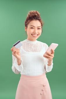 Belle jeune femme asiatique tenant un smartphone et une carte de crédit sur fond vert.
