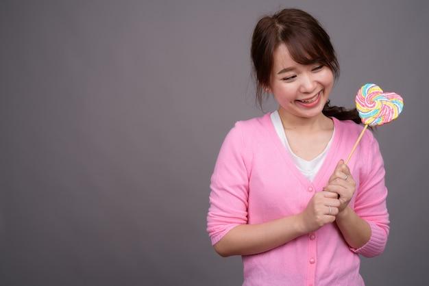 Belle jeune femme asiatique tenant une sucette colorée