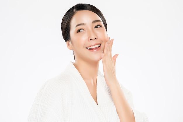 Belle jeune femme asiatique touchant la joue douce et sourire avec une peau propre et fraîche. bonheur et gai avec, isolé sur blanc, beauté et cosmétiques,