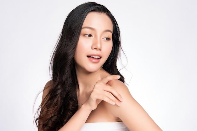 Belle jeune femme asiatique touchant son corps avec une peau saine et fraîche, isolée sur le mur blanc, les cosmétiques de beauté et le concept de traitement facial.