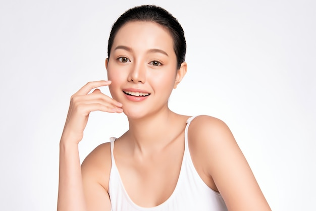 Belle jeune femme asiatique toucher son visage propre avec une peau saine et fraîche, isolée, cosmétiques de beauté et concept de traitement facial