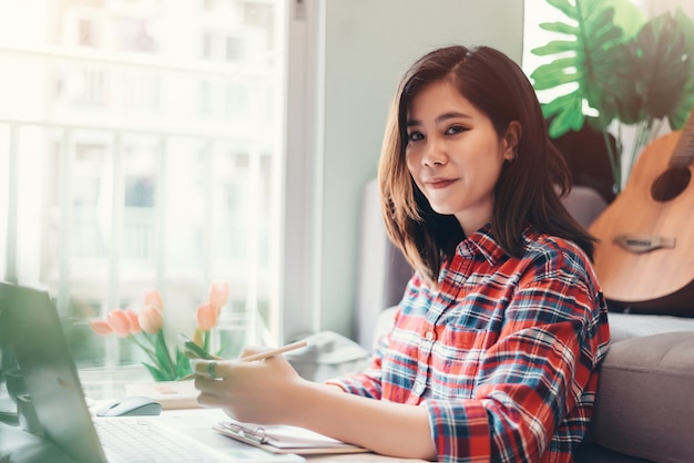 Belle jeune femme asiatique travaillant à domicile sur ordinateur portable