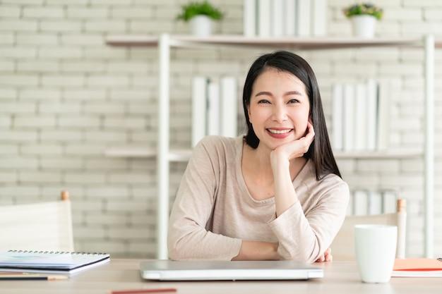 Belle jeune femme asiatique travaillant à domicile et se sentant heureuse en souriant avec une expression joyeuse