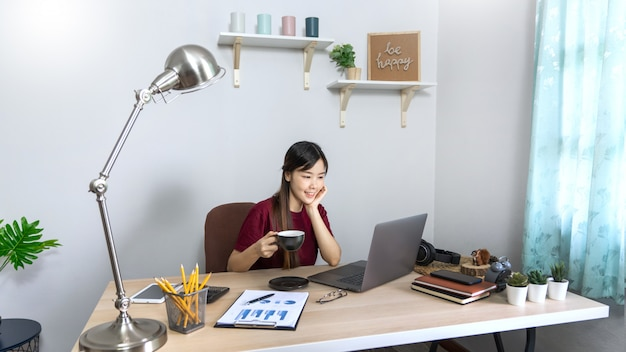 Belle jeune femme asiatique travaillant à la maison
