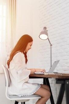 Belle jeune femme asiatique utilisant un ordinateur portable à la maison.