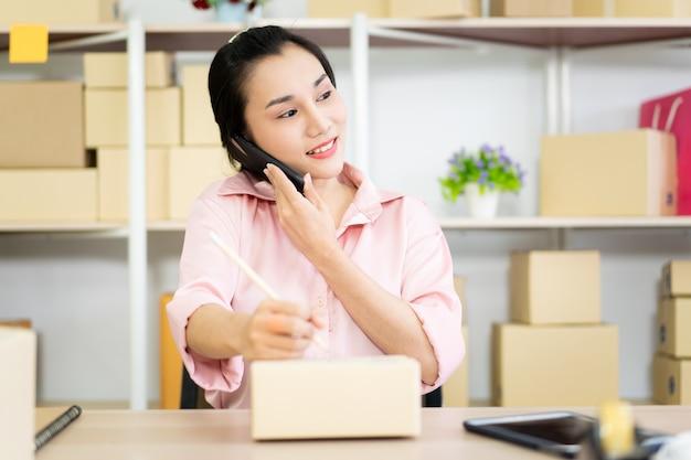 Belle jeune femme asiatique vendant des produits en ligne. jolie fille asiatique écrit l'adresse postale sur une boîte de colis papier.