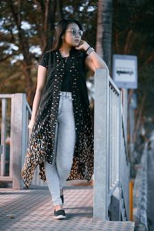 Belle jeune femme asiatique vêtue d'une robe authentique posant sur l'arrêt de bus par beau temps