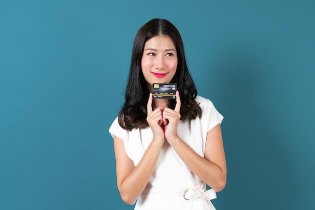 Belle jeune femme asiatique avec un visage heureux et présentant une carte de crédit en main montrant la confiance et la confiance pour effectuer le paiement sur bleu