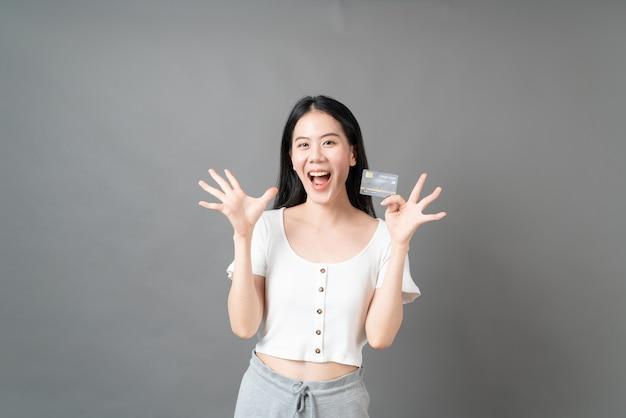 Belle jeune femme asiatique avec un visage heureux et présentant une carte de crédit en main montrant la confiance et la confiance pour effectuer le paiement
