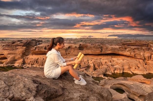 Belle jeune femme asiatique voyageur assis et regardant la carte papier sur la falaise rocheuse dans le grand canyon de la thaïlande au coucher du soleil