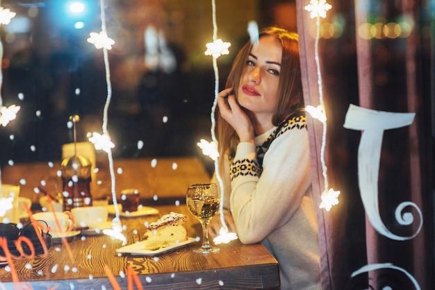 Belle jeune femme assise au café, boire du vin. noël, nouvel an, saint valentin, vacances d'hiver