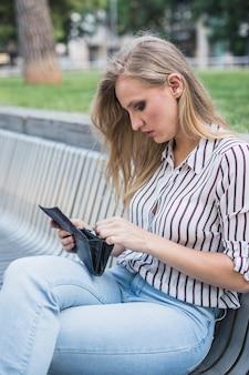 Belle jeune femme assise sur un banc en regardant le portefeuille