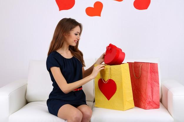 Belle jeune femme assise sur un canapé avec des sacs sur fond gris