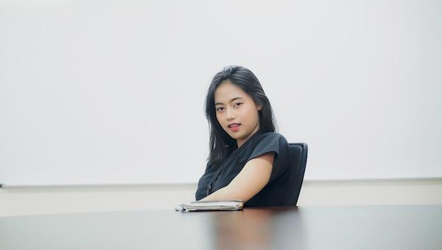 Belle jeune femme assise sur une chaise souriant gaiement