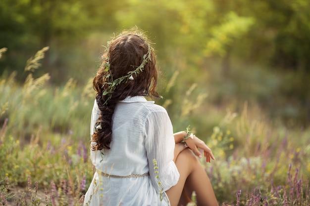 Belle jeune femme assise dans un champ de blé dans le concept de beauté et d'été du coucher du soleil d'été
