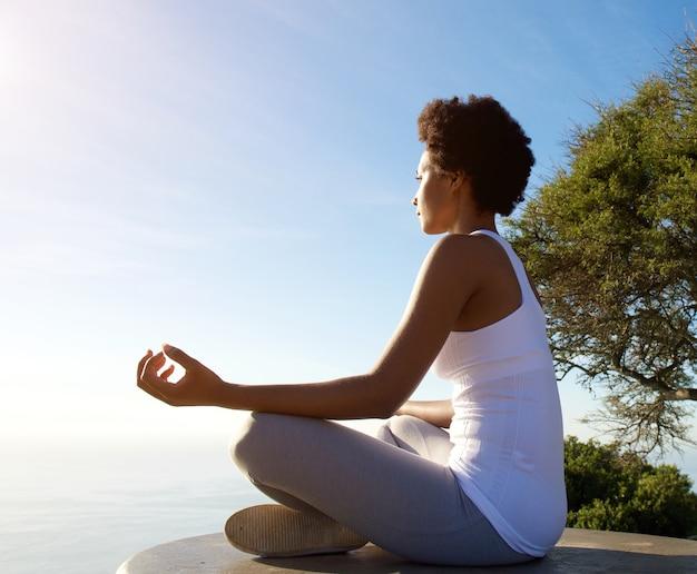 Belle jeune femme assise dans la pose d'yoga à la plage