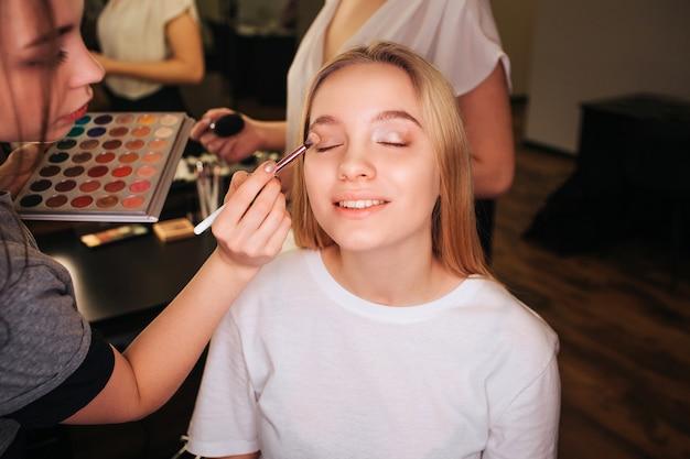 Belle jeune femme assise dans une salle de beauté avec les yeux fermés