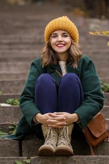 Belle jeune femme assise sur les escaliers à l'extérieur