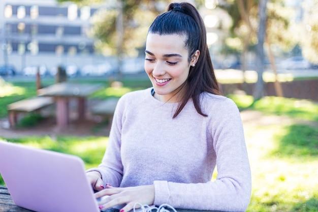 Belle jeune femme assise à l'extérieur tout en travaillant avec un ordinateur portable