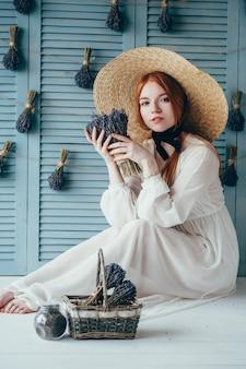 Belle jeune femme assise à la lavande contre le mur bleu.