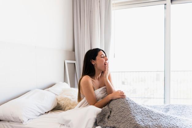 Belle jeune femme assise sur le lit en bâillant