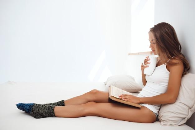 Belle jeune femme assise sur le lit, boire du thé, livre de lecture