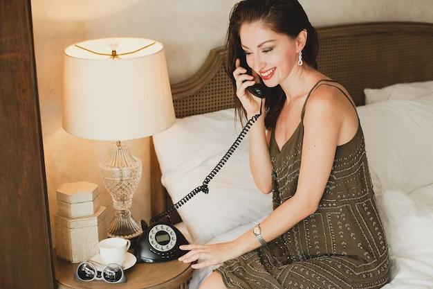 Belle jeune femme assise sur le lit à l'hôtel, robe de soirée élégante, humeur sensuelle, parler au téléphone, souriant, affectueux, à la recherche, sexy