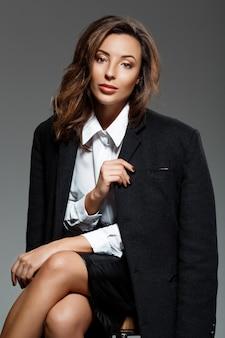 Belle jeune femme assise sur un mur gris
