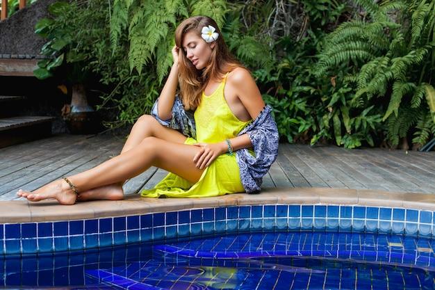 Belle jeune femme assise à la piscine en robe boho jaune, mode tendance estivale, sexy, maigre, peau bronzée, jambes minces, vacances tropicales, resort hotel, souriant, sensuel, voyage en asie, chaud,