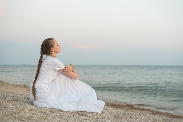 Belle jeune femme assise sur une plage de sable contre la mer et les rêves.
