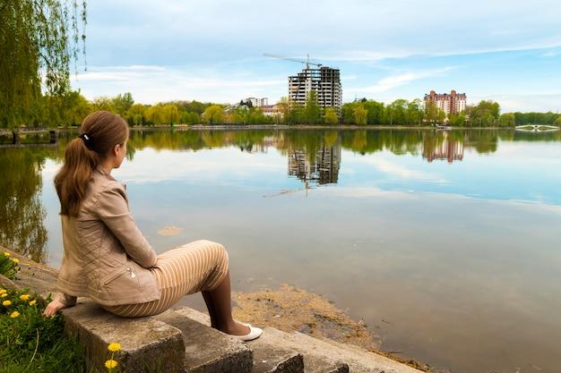 Belle jeune femme assise sur la rive du grand lac