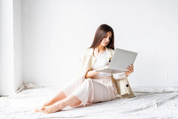 Belle jeune femme assise sur le sol et faisant un projet indépendant sur ordinateur portable, à l'aide d'un ordinateur