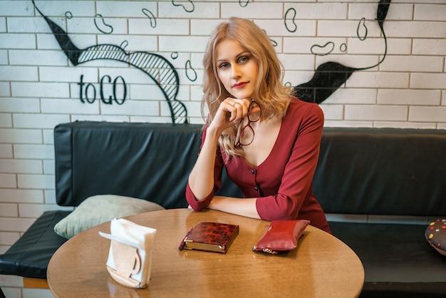 Belle jeune femme assise à une table avec un cahier et un téléphone.