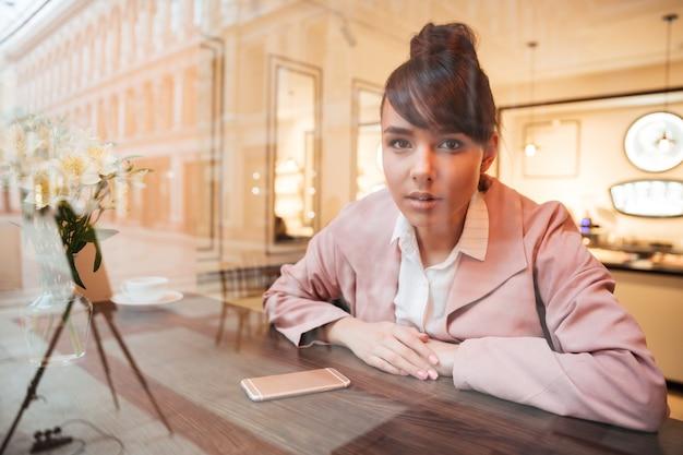 Belle jeune femme assise à la table du café
