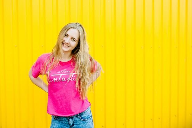Belle jeune femme athlétique aux longs cheveux blonds dans une chemise rose et un jean bleu. posant et souriant au mur du garage sur le mur jaune mains sur la ceinture. place pour le texte. fermer. sourires