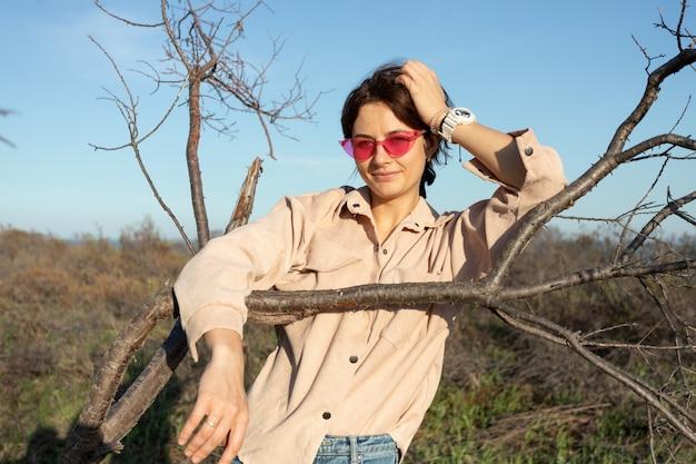 Belle jeune femme athlétique dans une chemise posant sur le fond de vieux arbres par une chaude journée d'été près de la mer. concept d'été. détente en forêt