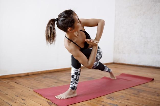 Belle jeune femme athlétique pratiquant le yoga en salle sur tapis rouge