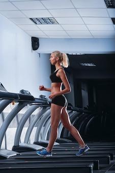Belle jeune femme athlétique qui court sur un tapis roulant au gymnase