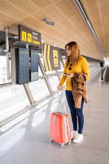 Belle jeune femme attendant à l'aéroport avec ses bagages