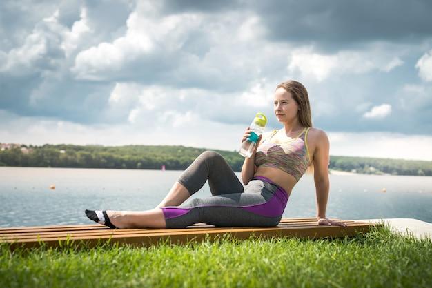 Belle jeune femme au bord du lac après l'entraînement avec une bouteille d'eau à la main