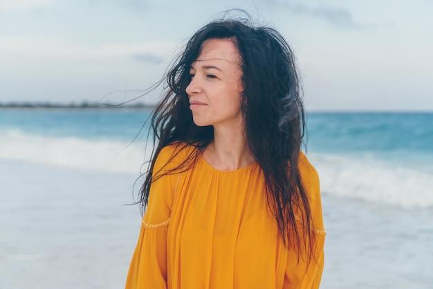 Belle jeune femme au bord de la mer tropicale au coucher du soleil.