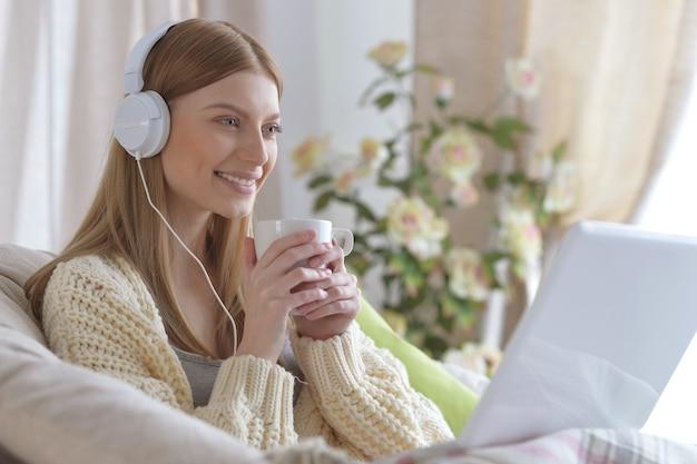 Belle jeune femme au casque à l'aide d'un ordinateur portable avec une tasse de thé à la maison