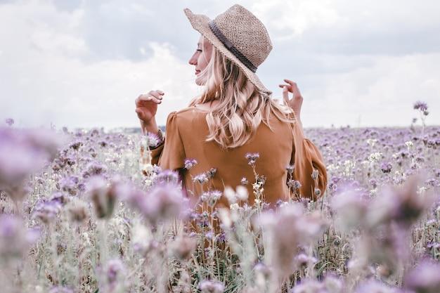 Belle jeune femme au chapeau en champ de lavande. fleurs en floraison
