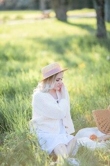 Belle jeune femme au chapeau en osier se repose sur un pique-nique dans un jardin fleuri. fleurs blanches. printemps. joie.
