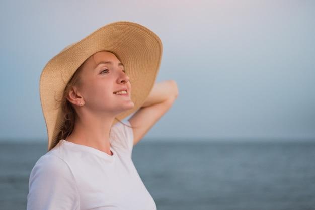 Belle jeune femme au chapeau de paille sur fond de mer. vacances nautiques