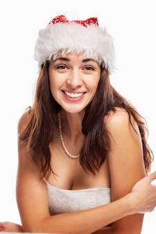 Belle jeune femme au chapeau de père noël rit. verticale. isolé sur blanc.