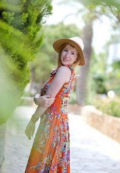 Belle jeune femme au chapeau et robe maxi jaune, journée ensoleillée, concept de liberté, vacances, nature tropicale
