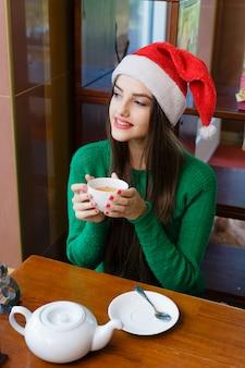 Belle jeune femme au chapeau rouge de pères noël, boire du thé au café