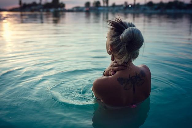 Belle et jeune femme au coucher du soleil dans le lac. repos du soir après une dure journée. eau du lac bleu laiteux et beau coucher de soleil